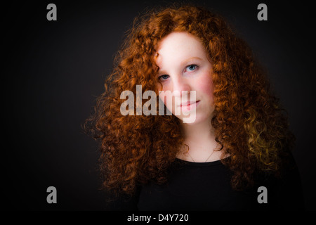 A young Pre-Raphaelite looking 16 year old teenage girl with ginger red long curly hair, UK - Stock Photo