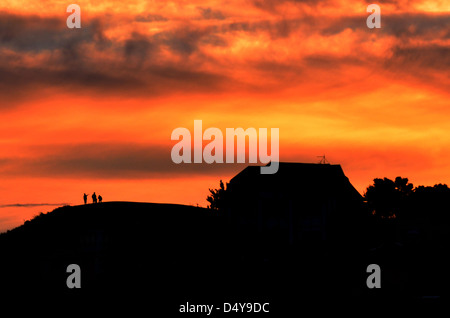 Dramatic sunset over family home. - Stock Photo