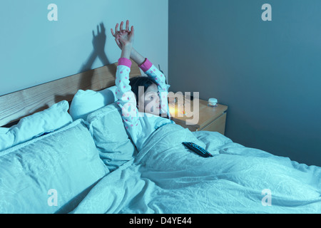Young girl watches TV in bed - Stock Photo