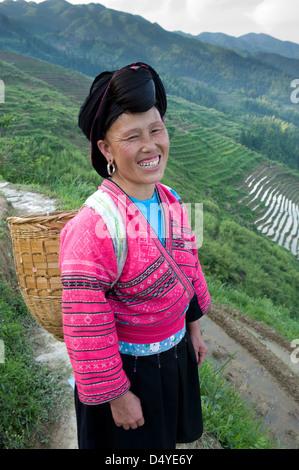 Yao Woman working in rice terraces, Dazhai Village, Dragon's Backbone Rice Terraces near Yao Guangxi Province China. - Stock Photo