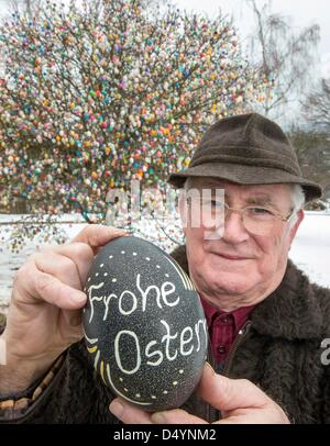 Volker Kraft poses with a big Easter egg in front of a tree decorated with Easter eggs in Saalfeld, Germany, 18 - Stock Photo