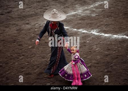 An escaramuza from El Pedregal team carries a little girl during an escaramuza fair in Mexico City - Stock Photo