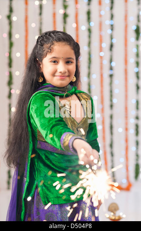 Girl burning fire crackers on Diwali - Stock Photo