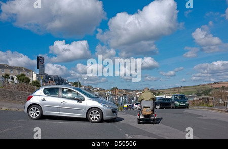 A man on a mobility scooter swerves down the road - Stock Photo