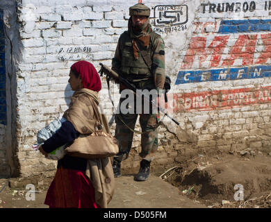 Srinagar, Indian Administered Kashmir, Thursday 21th March 2013. A Kashmiri Muslim woman walks as an Indian army - Stock Photo