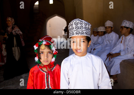 Young Omani school children in Traditional costumes on a school visit the Nizwa Fort in Oman - Stock Photo