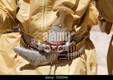 Traditional Omani Khanjar dagger worn in a sheath on a belt lined with bullets - Stock Photo