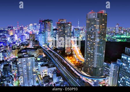Dense buildings in Minato-ku, Tokyo Japan with Tokyo Sky tree visible on the horizon. - Stock Photo