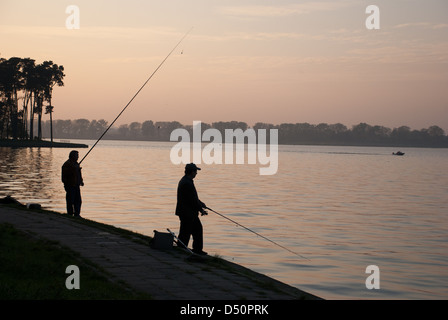 Silhouettes of men fishing at dusk - Stock Photo
