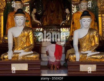 A woman praying in the Shwedagon Pagoda, Yangon, Myanmar, is dwarfed by four giant Buddha statues. - Stock Photo