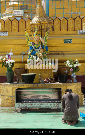 A young woman prays in front of a planetary post in the Shwemawdaw Pagoda in Bago, Myanmar. - Stock Photo