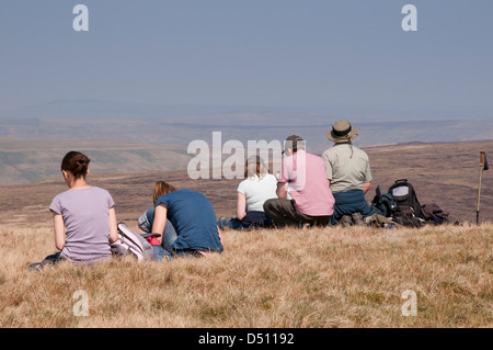 Rear view of people (walkers) sitting on high summit of Pen-y-ghent (one of Yorkshire Three Peaks) looking out over - Stock Photo