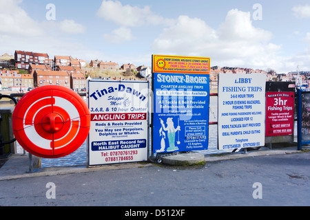 Notices advertising the several boats offering sea angling trips from New Quay at Whitby - Stock Photo