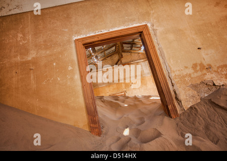 Sand piles up against walls and doors in the deserted ghost town of Kolmanskop in the diamond Sperrgebiet in Namibia. - Stock Photo