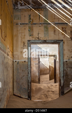 Light and sand invading the derelict houses of the old mining ghost town of Kolmanskop, Namibia. - Stock Photo