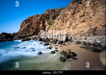 A secluded cover in Laguna Beach, California shows the seawater rushing to shore over smooth boulders. - Stock Photo