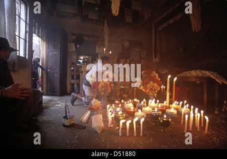 Locals pay respects to maximon at a candlelit shrine in Santiago Atitlan - Stock Photo