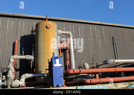 Exterior of modern industrial building with pipes and tank. - Stock Photo