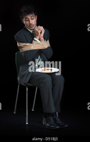 Businessman tied up with adhesive tape and looking to toast on a plate - Stock Photo