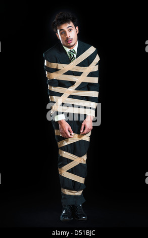 Businessman tied up with adhesive tape and looking sad - Stock Photo