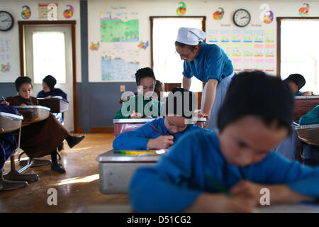 Dec 05, 2012 - Bergholz, Ohio, U.S. - An amish girl gets help from her teacher during a arithmetic lesson. (Credit - Stock Photo