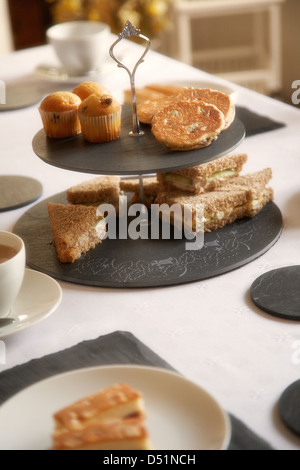 Afternoon tea table setting using welsh slate placemats and coasters in a home in south Wales, UK - Stock Photo