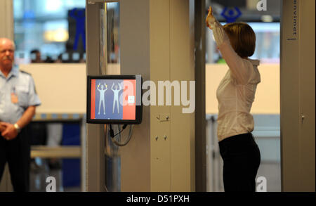 A woman walks through a body scanner at the airport in ...