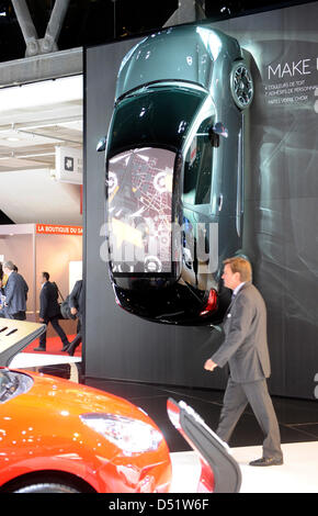 A man walks past a Citroen DS3 that is hanged to the wall during the 2010 Paris Motor Show in Paris, France, 30 - Stock Photo