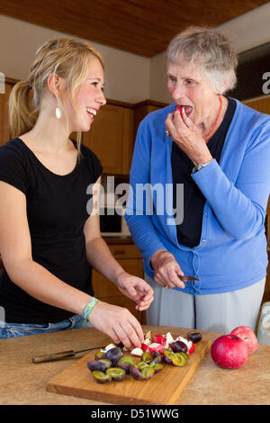 Senior Klara Fuerst (78) and student Sarah Boehm (20) cut fruit at the kitchen in Muenster, Germany, 14 September - Stock Photo