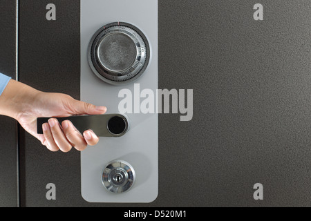 Hand opening a large safe - Stock Photo