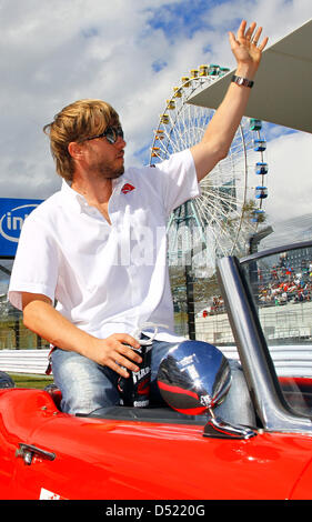 German formula one driver Nick Heidfeld waves to his fans during the drivers parade prior to the Japanese Grand - Stock Photo