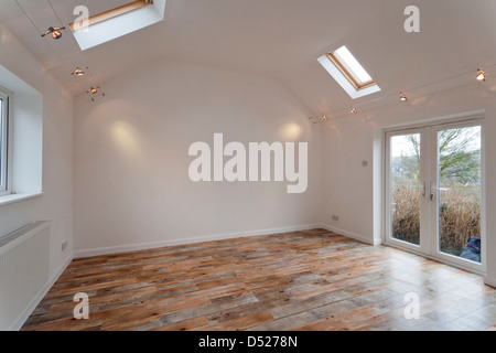 A large new unoccupied white painted high ceilinged empty room with Velux skylights. - Stock Photo