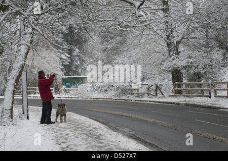 Man in wellies, hat & coat, has stopped with his dog, to take a photo of trees covered in white snow by a quiet, - Stock Photo