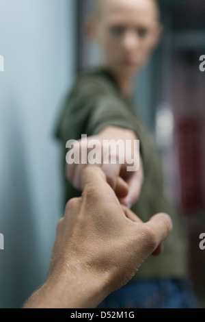 Man's hand reaching to hold woman's hand - Stock Photo