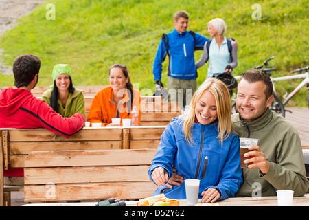 Cheerful people enjoying springtime weekend in rest area drinking beer - Stock Photo