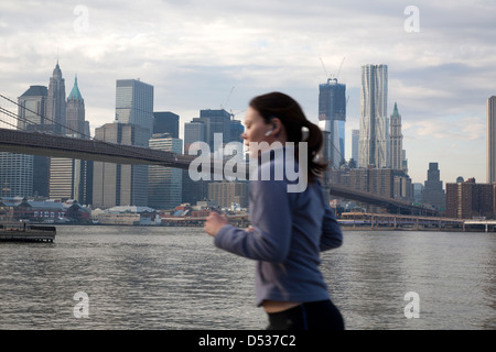 New York City, USA, female jogger on the banks of the East River with the Manhattan skyline - Stock Photo