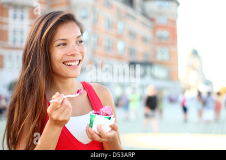 Joyful multicultural Asian Caucasian woman smiling and eating ice cream in front of Château Frontenac in Quebec - Stock Photo