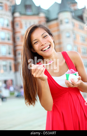 Joyful multicultural Asian Caucasian woman in red summer dress smiling and eating ice cream in front of Château - Stock Photo