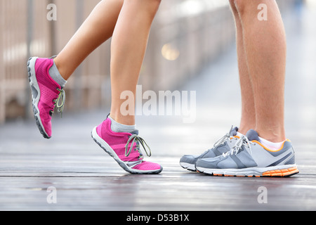 Low section of young interracial couple in sports shoes standing on brooklyn bridge, New York City - Stock Photo