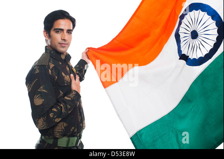 Portrait of an army soldier standing with a hand on his heart while holding Indian flag - Stock Photo
