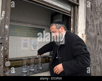 Religious Jewish man washing glasses in a Mikvah in the Crown Heights section of Brooklyn, New York - Stock Photo
