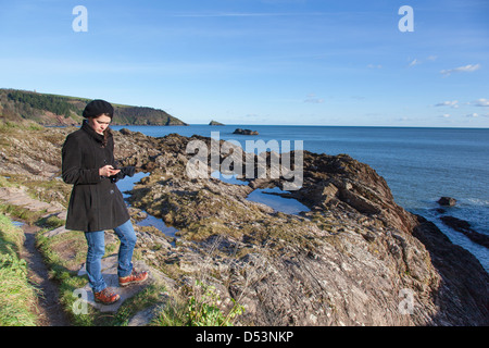 Girl dressed for winter in black coat and beret, checks her mobile phone whilst standing on rocks at the mouth of - Stock Photo
