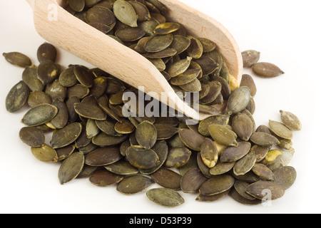 Pumpkin seeds in wooden spoon - Stock Photo