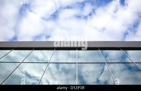 clouds and blue sky reflected in windows of office building - Stock Photo