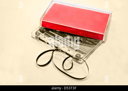 Two old cassette tapes with and without plastic cases on a sepia background. - Stock Photo