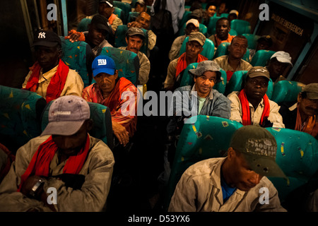 Sugar cane cutters sit on a bus while going to work on a plantation near Florida, Valle del Cauca, Colombia. - Stock Photo