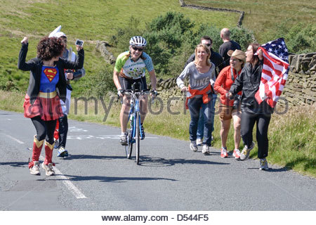 Supporters in fancy dress and with the USA flag encourage a female competitor taking part in the Bolton Ironman, - Stock Photo