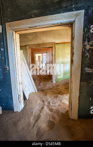 Desert invades in the houses in Kolmanskop where once the diamond workers lived near Lüderitz, Namibia. - Stock Photo