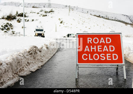 Police close a road because of very heavy snow drifts after a blizzard - Stock Photo