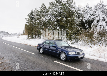A car drives along a rural road which has been cleared of snow - Stock Photo